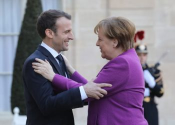 French President Emmanuel Macron (L) greets German Chancellor Angela Merkel (R) upon her arrival at the Elysee presidential Palace in Paris on March 16, 2018.  Days after securing her fourth term as Germany's leader, Chancellor Angela Merkel travelled to Paris to meet French President Emmanuel Macron, but their push to reform the European Union was met with warnings from smaller members of the bloc. / AFP PHOTO / LUDOVIC MARIN